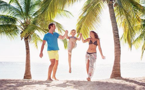 Young family on beach vacation with palm trees in background
